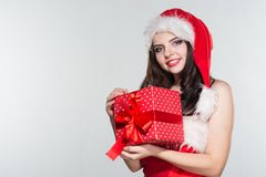 Merry Christmas. Beautiful young woman in a red Mrs. Claus costume and Santa cap. Holding gift box on a white background royalty free stock photography