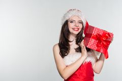 Merry Christmas. Beautiful young woman in a red Mrs. Claus costume and Santa cap holding gift box. On a white background royalty free stock photography