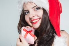 Merry Christmas. Beautiful young woman in a red Mrs. Claus costume and Santa cap holding gift box. On a white background stock photo