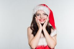 Merry Christmas. Beautiful young woman in a red Mrs. Claus costume and Santa cap holding hands near the face on her cheeks. On a white background stock images