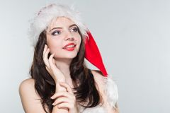 Merry Christmas. Beautiful young woman in a red Mrs. Claus costume and Santa cap holding hands near the face on her cheeks. On a white background royalty free stock photography