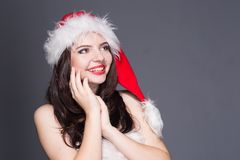Merry Christmas. Beautiful young woman in a red Mrs. Claus costume and Santa cap holding hands near the face on her cheeks. On a white background stock image