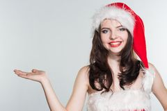 Merry Christmas. Beautiful young woman in a red Mrs. Claus costume and Santa cap holding her hand palm up. On a white background royalty free stock image
