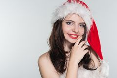 Merry Christmas. Beautiful young woman in a red Mrs. Claus costume and Santa cap. On a white background royalty free stock image