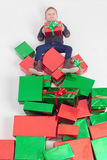 Merry Christmas 2016. Black friday. Happy boy holding Cristmas gift. At the top of many gift boxes. Child happy to receive present. Shopping sale at Xmas. Cyber Royalty Free Stock Images