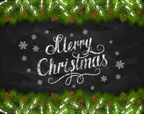 Merry Christmas on blackboard with fir tree branches. Lettering Merry Christmas written in white chalk with snowflakes, fir tree branches and pine cones on a Stock Photo