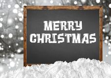 Merry Christmas on blank blackboard with blurr forest and snow Stock Photo