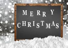 Merry Christmas on blank blackboard with blurr forest and snow Royalty Free Stock Photo