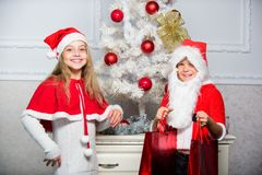 Merry christmas. Boy kid dressed as santa with white artificial beard and red hat give gift box to girl. Kids celebrate stock photo