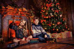 Merry christmas. Brother and sister playing with a toy railway near the Christmas tree and fireplace. Christmas night. Christmas decoration Stock Images