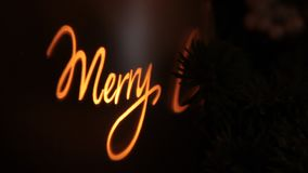 Merry Christmas lights in candle glass. Merry Christmas candle and tree lights dark night background in home living room stock video