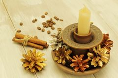 Elements of decor. Christmas. Ceramic candlestick with candle, colorful pine cones, fragrant cinnamon sticks, roasted coffee be royalty free stock images