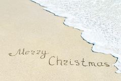 Merry Christmas caption at wet beach sand with sea wave Stock Image