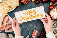 Merry christmas card. Cropped shot of person holding merry christmas card above festive decorations Stock Image