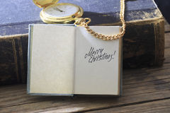 Merry Christmas Card. Merry Christmas - inscription, gold pocket watch and old vintage book royalty free stock image