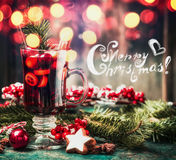 Merry Christmas card with mulled wine, cookies and holiday decorations on table with bokeh. Lighting Royalty Free Stock Photos