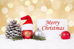 Merry Christmas card with ornaments, golden background and hat d. Merry Christmas card with ornaments, golden background, red balls and hat decoration royalty free stock photos