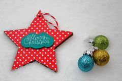 Merry christmas card with red star and colourful ornaments. Blue, green and yellow shiny ornaments to be put on the xmas tree Royalty Free Stock Images