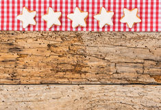 Merry Christmas card with star biscuits. Christmas star biscuits on checkered fabric and old wooden background Stock Images