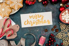 Merry christmas card. Top view of merry christmas card and festive decorations on black Stock Photos