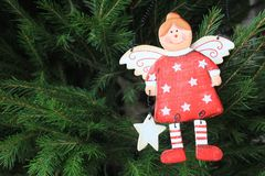 Merry christmas card with wooden angel. On the xmas tree Stock Images