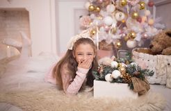 Merry Christmas celebration. Beautiful little girl in a dress lying near the Christmas tree. stock photography