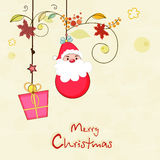 Merry Christmas celebration poster with hanging santa and gift. Royalty Free Stock Photo