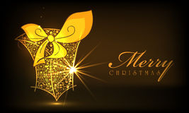 Merry Christmas celebrations with gift box. Floral decorated shiny gift box in golden color on brown background for Merry Christmas celebrations Stock Photo