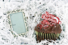 Merry Christmas Chocolate Cup Cake and Gift Tag. One chocolate, Christmas decorated, cupcake in silver and white paper with a gift tag Royalty Free Stock Photos
