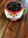 Merry Christmas,coffee beans in Cute Santa Claus Cup. On the wooden table Stock Photo