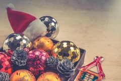Merry Christmas concept with balls in box, Santa Claus hat and little house royalty free stock photos