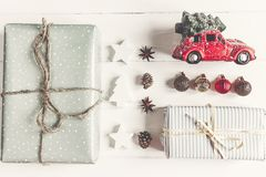 Merry christmas concept, flat lay. modern presents with car carr. Ying tree, ornaments  on rustic white wood top view. seasonal greetings. happy holidays. xmas Stock Image