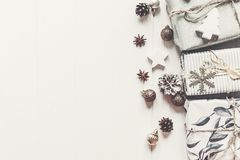 Merry christmas concept. stylish modern presents with ornaments. Cones anise on  rustic white wooden background top view, space for text. seasonal greetings Royalty Free Stock Photo