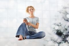 Merry Christmas concept young woman listens to christmas songs from her mobile phone with ear phones sitting at home with stock photography