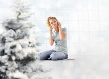 Merry Christmas concept young woman listens to christmas songs from her mobile phone with ear phones sitting at home with royalty free stock image