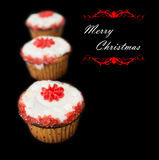 Merry Christmas cup cakes. Card against black background Stock Photos