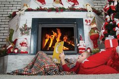 Merry Christmas!Cute boy reading a book lying on the carpet near the fireplace. stock image
