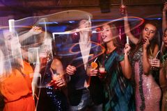 Merry Christmas dance party in night club. Happy friends company in motion, New Year celebration. Disco people in blurred colors, modern youth life Royalty Free Stock Photography