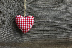 Merry Christmas Decoration Gingham Fabric Heart. Christmas handmade decoration gingham fabric hearth over rustic Elm wood background - retro style design, copy Stock Photos