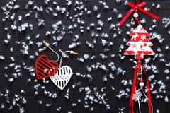 Merry Christmas decorations, snowflakes, white red hearts and toy xmas tree on black wooden background card, top view Stock Photo