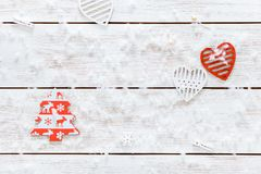 Merry Christmas decorations, snowflakes, white red hearts and toy xmas tree on light wooden background card, top view Stock Image