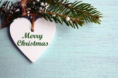 Merry Christmas.Decorative white wooden Christmas heart and fir tree branch on blue wooden background.Winter holidays concept. Selective focus Stock Image