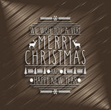 Merry Christmas design greeting card. Handwritten text on wooden background. Happy New Year message Royalty Free Stock Photos