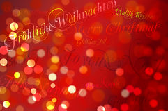 Merry Christmas in different languages. On a Bokeh Background Stock Photography