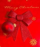 Merry Christmas Display in Red and Gold. Merry Christmas in gold script and red decorative ornament and bow stock photo