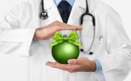 Merry Christmas from doctor,, best wishes concept, hands with xmas green ball, gift card banner web template with copy space royalty free stock photography