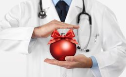 Merry Christmas from doctor,, best wishes concept, hands with xmas red ball, gift card banner web stock photography
