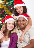 Merry Christmas family. Merry Christmas: Happy young multi racial family sitting by Christmas tree Royalty Free Stock Photography