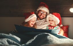 Merry Christmas! family father reads to children book before bed royalty free stock images