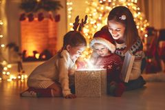 Merry Christmas! family mother and children with magic gift at. Home near Christmas tree and fireplace royalty free stock photos